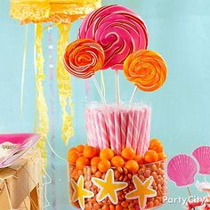 "A candy ""cake"" in tropical colors = fab summer candy buffet centerpiece. Make it with gumballs, candy sticks and giant lollies. Sweet!"