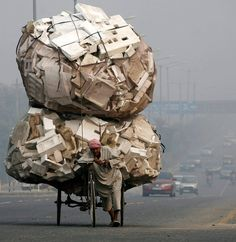 A man pulls his trishaw loaded with used polystyrene during a foggy day on a busy street in New Delhi