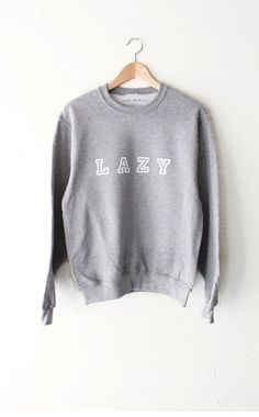 "- Description - Size Guide Details: Soft & cozy oversized sweater in grey with print featuring 'Lazy'. Oversized, Unisex fit. Brand: NYCT Clothing. 50% Cotton, 50% Polyester. Imported. Sizing: 40"" / 1"