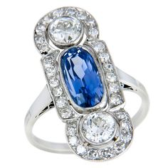 Edwardian Platinum, Diamond and Sapphire Ring, set with an Oval-Cushion Ceylon Sapphire, approximately 1 carat. and further set with 2 old European cut Diamonds totaling .90 carat and surrounded by approximately 1 Carat of smaller old European cut Diamonds. circa 1920.