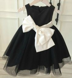 Large Bow Front Dress-Made To Order - High Quality Elegant Unique Fashionable Sweetheart Neckline Sleeveless Knee Length Large Bow Front Sash Belt Baby Infant Toddler Little & Big Girl Party Dress. Available from 9 months until 13 years. Material: Satin, polyester fiber, tulle mesh, cotton. Color: Black. Please do compare your little girl measurements with our size chart.