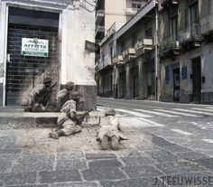 """Ten miles north of Catania, Italy, two British Bren gunners and their assistants cover a street corner on the Via Vittorio Emmanuele II in Acireale, Sicily, 1943."" Combined photo of then and modern location by Jo Hedwig Teeuwisse."