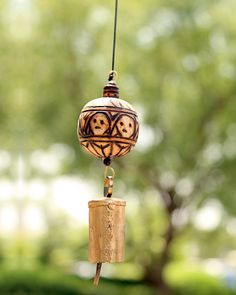 A rustic hand crafted wind chime. Etched wood and hand beaten copper bell.