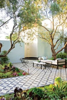 Beneath the olive trees, a Heath Ceramics-tiled water feature with Plain Air furniture and striking encaustic Granada Tile underfoot. PHOTO: Erik Otsea.