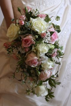 Romantic trailing bouquet in soft pink and white, including roses, spray roses, and viburnum.