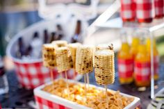 Corn on the cob on skewers; skewers are inserted into styrofoam, which is camouflaged by a layer of Fritos.