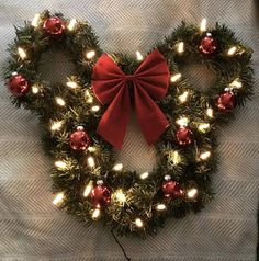 An adorable Christmas-themed Mickey (or Minnie!) wreath for all of the Disney lovers out there! This Mickey-shaped wreath is made using artificial pine garland and is pre-lit with clear string lights (a battery operated option is available in the drop-down menu). It is decorated with
