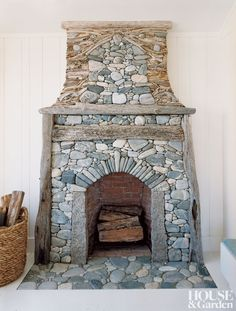 a fireplace of water-worn stones laced w/ driftwood by Lew French