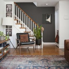 Dark paint in stairwell, photos in entryway. Check this out: A Modernized Charmer For Creatives in Pennsylvania. https://re.dwnld.me/6jDv3-a-modernized-charmer-for-creatives-in-pennsylvania