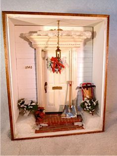 Miniature 8 1/2x11 room box depicting a front door with Christmas decorations and sled with snow.   Materials: Wood, styrofoam, metal, brick, sisal. Only 1 available.  -  Our Price: $110.00 USD