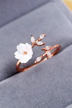 Spring Wedding Sakura Blossom Ring This beautiful ring can help pull your whole wedding aesthetic together. With a flower made from shell, leaves decorated with zircon gems, and a rose gold band made to look like a branch wrapping around your finger, this ring is both nostalgic and modern. #wedding #sakura #cherry #flower #floral #ring #jewelry