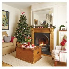 Cozy Christmas living room with corner tree. Country cottage holiday style with antique wooden chest, fireplace & handmade decorations. Red, white & green colors. Rustic simple life.
