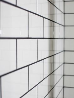 Glossy white 3x6 tiles laid in a subway pattern line the shower wall, with a deep, dark gray grout that creates a striking contrast and pattern.