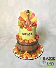 Completely edible Thanksgiving cake with wafer paper feathers, fondant pumpkins and hand painted autumn leaves. Fall green, red, orange and gold colors with sugar turkey on top.