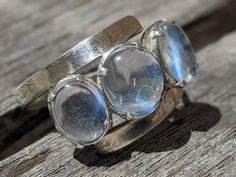 Ceylon Blue Moonstone band ring in Sterling Silver with such clear blue moonstones. I think this ring was handmade- it doesnt have silver marks but I have tested it. Very simple, slightly diagonal design with silver borders to the three moonstones. The central moonshine is about 7 mm by 6 mms and