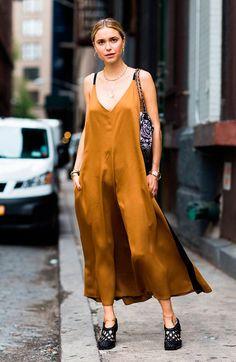 Pernille Teisbaek usa slip dress dourado com sapato mule preto e bolsa estampada