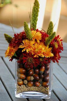 Sencillos centros de mesa, una base de cristal semillas y algunas flores.