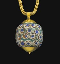 A PHOENICIAN OR CARTHAGINIAN GLASS BEAD   CIRCA 4TH CENTURY B.C.   Spherical in form, blue-green in color, with four rows of stratified eyes, each eye in four layers blue on white on amber on white; set as a pendant in a modern gold mount, suspended from a chain  1 in. (2.5 cm.) diameter