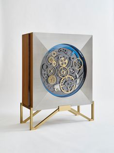 Maria Pergay 'Cabinet Engrenage' (2016) Brushed stainless steel facade; cabinet and interior drawers in lemon wood; base in brushed and polished brass; gears in Ti-black, Ti-blue and mirrored stainless steel 55.2 H x 44.09 x 19.69 inches 140.2 H x 112 x 50 cm Edition 1 of 8, with 4 APs