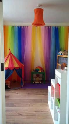 Rainbow wall curtain. Playroom space. IKEA circus tent. Kallax storage solution. Mid sleeper bed hideaway. Grimms wooden toys. Grimms rainbow, cars, 12 rainbow people and balls.
