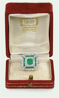 A BELLE EPOQUE EMERALD AND DIAMOND RING, BY CARTIER  The square-cut emerald within an old-cut diamond surround to the calibré-cut emerald frame, diamond border and two-stone corners, circa 1915, in Cartier red leather case