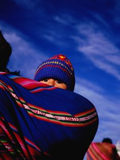 A young child wrapped in an aguayo, a traditional sling, on mother's back in La Paz, Bolivia.