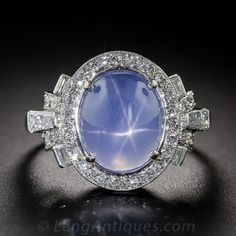 Raymond Yard Art Deco Blue Star Sapphire and Diamond Ring. By one of America's most-celebrated 20th century jewelers, an entrancing blue star sapphire, with a faint violet cast, measuring just under five carats (and presenting larger due to its flat bottom cut) and displaying a vivid six-legged star (a/k/a/ asterism) is elegantly presented in platinum. The stellar gemstone is orbited by tiny Swiss-cut diamonds and glows between round and baguette diamond-set rays