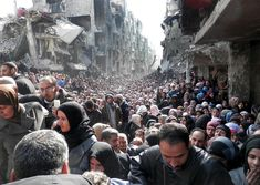 Residents of the besieged Palestinian refugee camp of Yarmouk line up to receive food supplies in Damascus, Syria