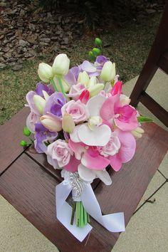Lindo e maravilhoso Bouquet de noiva de flores em silicone  e rosas em e.v.a todas apresentam o toque real de uma rosa real!    Bouquet noiva contém tulipas de silicone, orquídeas em silicone, e rosas em e.v.a nos tons branco, rosa e lilás    Perfeita e bela combinação de cores suaves e claras, contém 3 hastes de orquídeas, nas cores branca, lilás e rosa, com tulipas brancas, rosa e lilás salpicados de rosas lilás!    Bouquet envolto de fita branca, cabo aparecendo e um belo broche dá o ...