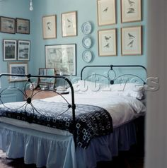 Country style bedroom with ornate cast iron bedstead and light blue ...