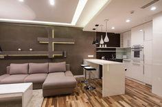 Salon połączony z kuchnią w kolorach bieli i brązu płytki ceramiczne na ścianie
