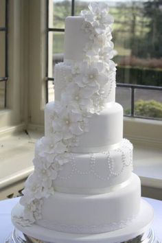 white wedding cakes | tier round white cake with white flowers draping down, classic style