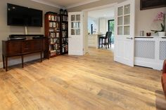 Winchester Antique engineered oak wood flooring with an aged and distressed surface to replicate a reclaimed oak board. Fitted throughout ground floor in Sunningdale Berkshire. Shown here in Kitchen & Living Room.
