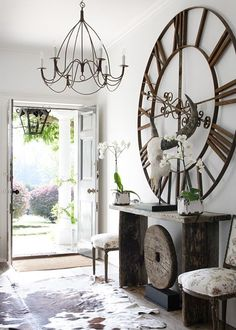 Love the rustic wood console table and the huge clock.