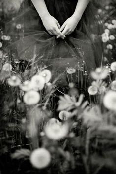 black + white photo in flower field. focus on hands and dress.