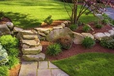 A rock garden with mulch highlights a slope in the front yard. #cottagelandscapefrontyard