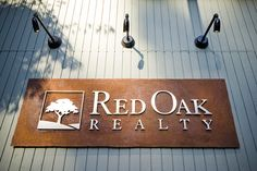 Real estate office signage. Manually aged and rough-cut coreten steel with raised stainless steel letters. Produced by Berkeley Signs, located at Red Oak Realty's Montclair office at 6450 Moraga in Oakland.