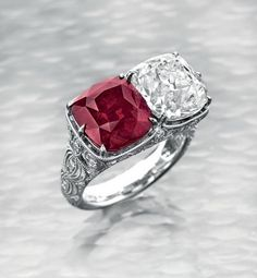 A Rare Ruby and Diamond Twin-Stone Ring Set with a cushion-cut ruby, weighing approximately 7.03 carats, and an old mine-cut diamond, weighing approximately 5.00 carats, to the single-cut diamond pierced gallery and shoulders, mounted in 18k white gold With report CS 62050 dated 10 July 2014 from the American Gemological Laboratories stating that it is the opinion of the Laboratory that the origin of this ruby would be classified as Mozambique. Heat enhancement: None