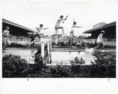 Black and white photo of runners at the water jump during the 3000 meter steeplechase at the 1971 AAU Championships held June 25-26 at Hayward Field. Mike Manley won, representing the Oregon Track Club. Identifiable are Steve Savage (2nd from left) and Barry Brown (4th from left). ©University of Oregon Libraries - Special Collections and University Archives