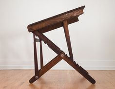 An interesting study in the development of the drafting table design. I particularly like the one in the photo selected because it seems like it could fold flat when not in use (unlike the later A frame ones, which provide more leg room for sitting).