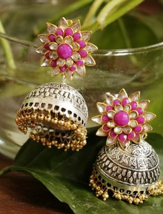 These earrings with a cute floral design and amazing work in golden shade makes them a perfect choice for parties and events. The beads at the bottom of the silver jhumkas are finished in gold tone wh