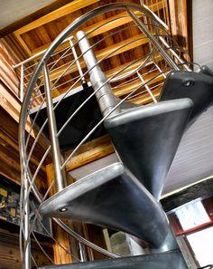 BH1 - SPIR'DÉCO® Béton en Ductal®. Escalier hélicoïdal d'intérieur design en béton ciré installé dans un chalet en bois. Marches en Ductal® teinte gris foncé minéral. Rampe sur mesure, ici version rampe contemporaine en inox brossé présentée (version acier brut possible sur demande). Main courante en tube ergonomique débillardé, 4 sous-lisses parallèles soulignant les courbes du colimaçon, montants en tubes. Rampe conforme normes NF P01-012. Ø 1,500 m. - Modèle déposé - © Photo : Studio…