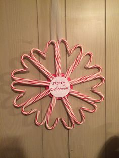 Candy cane wreath! Cute and easy Christmas craft. I taped the backs together then hot glued them to the card stock paper and hug it up with tulle