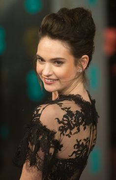 Make a dreamy updo more romantic by letting wispy pieces frame your face like Lily James did.
