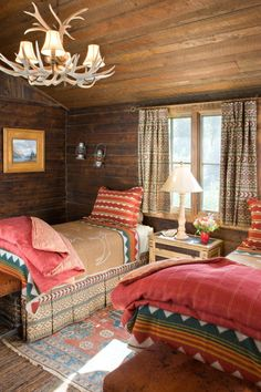 Vibrant textiles pop against wood paneling in sun-soaked 1917 Montana Cabin built by Jack Watkins' father - who was involved in constructing Old Faithful Lodge [660 x 990]