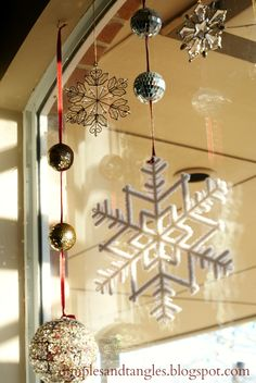 disco ball and snowflake ornaments strung in windows