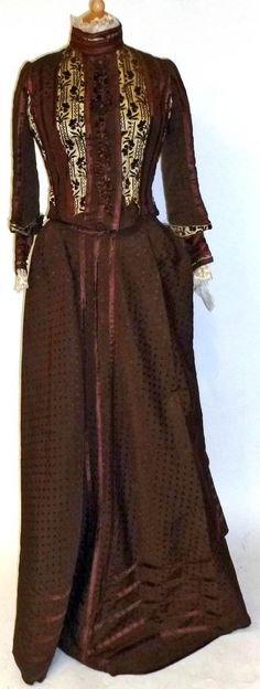Day dress, ca. 1870s. Two pieces in brown grosgrain silk with spot detailing. Fitted bodice has inserts of brown cut velvet on cream satin & brown silk striped appliqués. Lace mounted collar and cuffs, with matching skirt and silk trims at hem. Tennant's