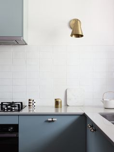 modern kitchen with colored cabinets and brass sconce