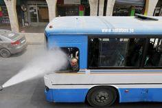A bus driver is sprayed with water to combat the heat in Jordan. (Muhammad Hamed / Reuters)
