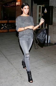 Kourtney Kardashian wears a gray sweater, gray jeans, a quilted backpack, and peep-toe booties